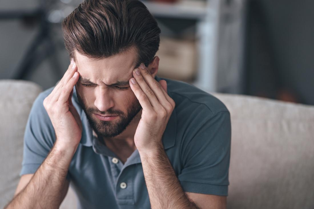 man with migraine headache massaging his temples and frowning