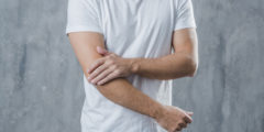 mid section man having elbow pain standing against grey background 23 2147948398